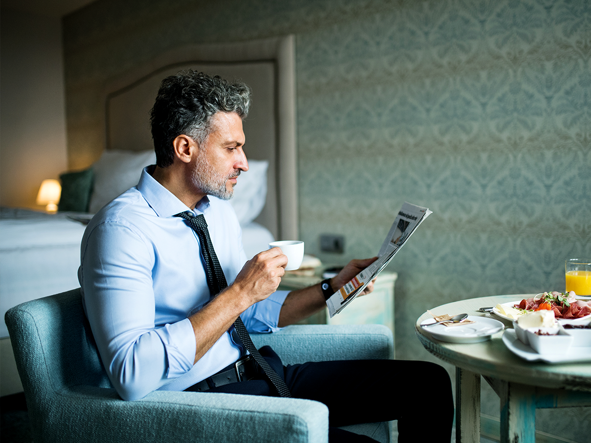 Business man drinking coffee while reading a newspaper
